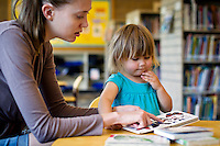 JEROME A. POLLOS/Press..Tamara Kermelis reads to her daughter River Kermelis, 2, during a visit Monday to the Coeur d'Alene Public Library.