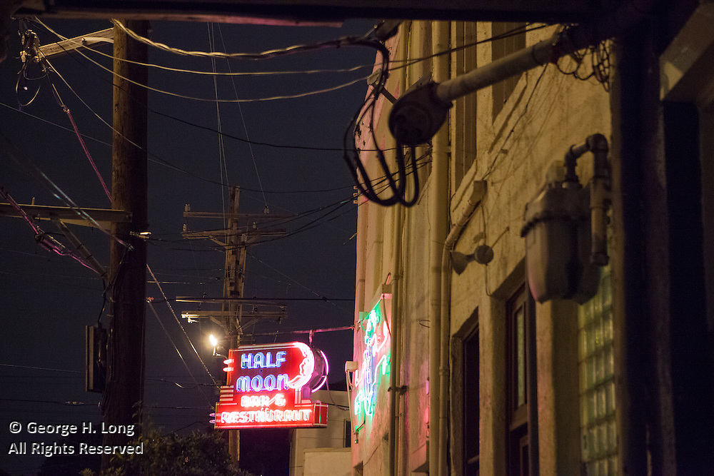 Neon sign and utility lines at Half Moon Bar & Restaurant; Camp Street at St. Mary Street