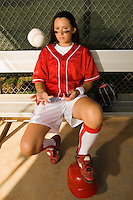 Softball Player Tossing Ball in Dugout