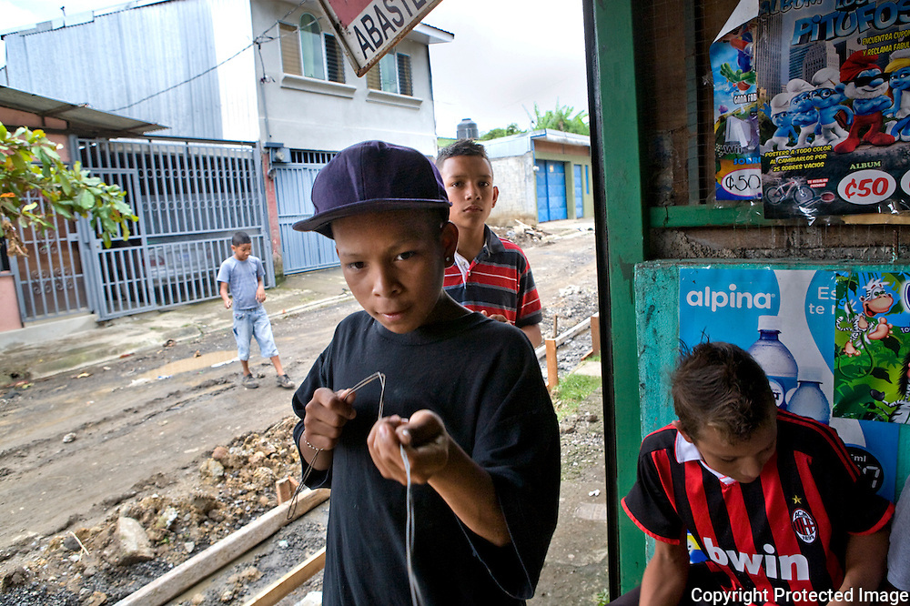 Kevin and his friends play at making guns from barbed wire they found in the street outside a corner in San Felipe.
