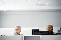 Two businessmen sitting face to face in office cubicle smiling side view