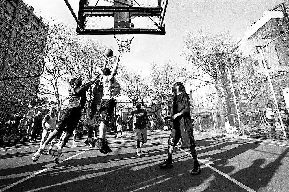 "April 10th 2005. New York, New York. United States..Located in the heart of Greenwich Village, the West 4th Street basketball Court, known as ""The Cage"", offers no seating but attracts the best players and a lot of spectators as soon as spring is around the corner..Half the size of a regular basketball court, it creates a fast, high level of play. The more people watch, the more intense the games get. « The Cage » is a free show. Amazing actions, insults and fights sometimes, create tensions among and inside the teams. The strongest impose their rules. Charisma is present..""The Cage"" is a microcosm. It's a meeting point for the African American street culture of New York. Often originally from Jamaica or other islands of the Caribbean, they hang out, talk, joke, laugh, comment the game, smoke… Whether they play or not, they're here, inside ""The Cage"". Everybody knows everybody, they all greet each other, they shake hands and hug: ""Yo, whasup man?"""