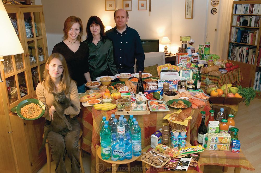 (MODEL RELEASED IMAGE). The Le Moine family in the living room of their apartment in the Paris suburb of Montreuil, with a week's worth of food. Michel Le Moine, 50, and Eve Le Moine, 50, stand behind their daughters, Delphine, 20 (standing), and Laetitia, 16 (holding spaghetti and Coppelius the cat). Cooking methods: electric stove, microwave oven. Food preservation: refrigerator-freezer. Favorite foods? Eve: fresh vegetables. Delphine: Thai food. Laetitia: pasta carbonara. /// The Le Moine family is one of the thirty families featured in the book Hungry Planet: What the World Eats (p. 124). Food expenditure for one week: $419.95 USD. (Please refer to Hungry Planet book p. 125 for the detailed food list.)