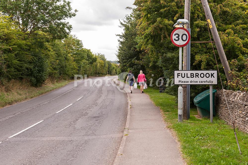 People walk into the village of Fulbrook near Burford , Oxfordshire , England , Britain , Uk