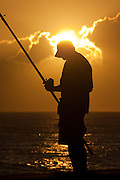 Lone fisherman at sunset in Hawaii