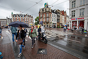 Een man op een snorscooter rijdt op het fietspad bij het Muntplein in Amsterdam vlak achter overstekende voetgangers.<br /> <br /> A man on a scooter passes at the Munt Square in Amsterdam crossing pedestrians on the bike lane.