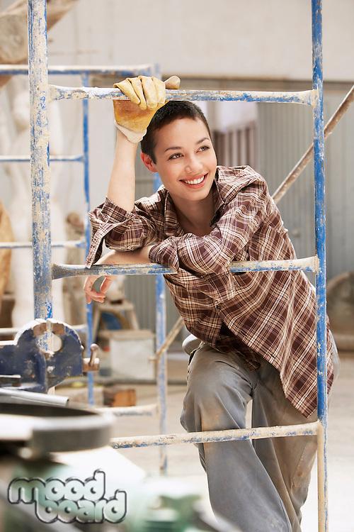 Female interior decorator leaning on Scaffolding