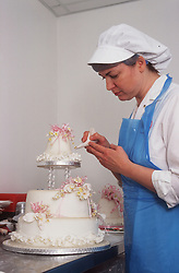 Trainee chef icing wedding cake,