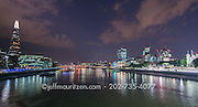 A panoramic image of the River Thames, Tower of London and the Shard lit up at night.