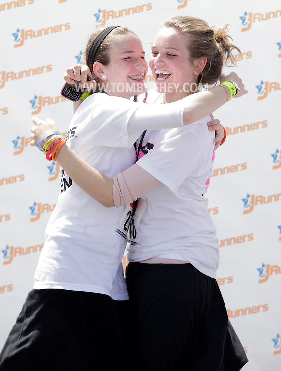 Nechama Friedman, left, and Libbi Mendelovitz hug each other after getting their age-group awards at the JRunners 5K Run Walk for Women at Sullivan County Community College in Loch Sheldrake on Wednesday, July 27, 2011.