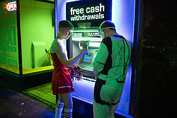© Licensed to London News Pictures . 26/12/2018. Wigan, UK. Two man withdraw cash from an ATM . Revellers in Wigan enjoy Boxing Day drinks and clubbing in Wigan Wallgate . In recent years a tradition has been established in which people go out wearing fancy-dress costumes on Boxing Day night . Photo credit: Joel Goodman/LNP