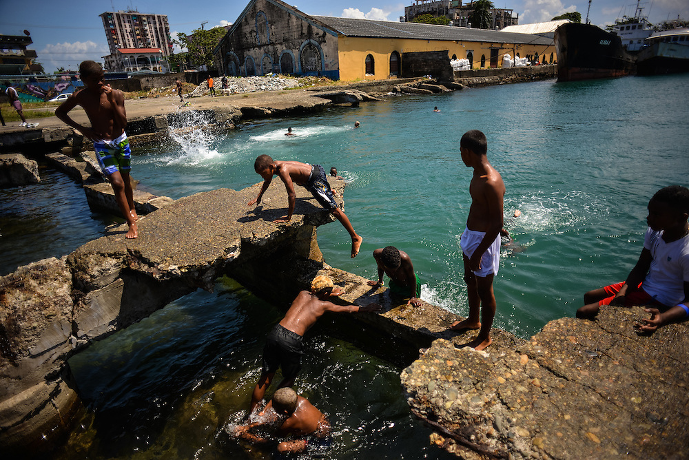 Children play and swim among a crumbling concrete dock in Colón, Panama. Despite being the second largest city in Panama, Colón is one of the poorest in the region, and its residents suffer from a critical shortage of potable water, sewer connections and housing--many people live in condemned or should be condemned buildings. Panama is now one of the fastest growing countries in Latin America and there is a growing resentment and impatience that Colón has not reaped as much of the benefit as Panama City.