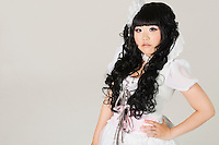Portrait of cute young woman in doll costume standing over gray background