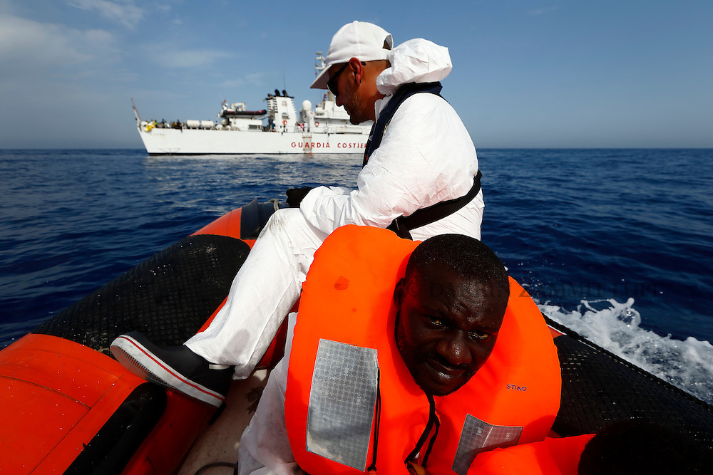 A Migrant Offshore Aid Station (MOAS) RHIB (rigid hulled inflatable boat) carrying rescued migrants approaches the Italian Coast Guard Vessel Oreste Corsi off the coast of Libya, August 3, 2015.  118 migrants were rescued by the MOAS ship MV Phoenix from a rubber dinghy some 20 miles (32 kilometres) off the coast of Libya on Monday morning. The Phoenix, manned by personnel from international non-governmental organisations Medecins san Frontiere (MSF) and MOAS, is the first privately funded vessel to operate in the Mediterranean.<br /> REUTERS/Darrin Zammit Lupi <br /> MALTA OUT. NO COMMERCIAL OR EDITORIAL SALES IN MALTA