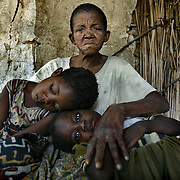 Meamui Wanalu, who doesn't know her age, sits with her two HIV positive granddaughters  Lungowe, 7 (left), and Adina, 6. Wanalu raises 4 grandchildren, two of which are HIV positive, and on ART. She lives in a decrepit hut that a villager lets her use and relies on World Food Program rations and charity from neighbors to care for her orphans. The World Food Program provides nutritional support to the ART program, but the rations are scheduled to run out at the end of April, unless donors come through with money to buy food locally or find another way of getting food to Zambia quickly.