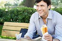 Businessman with sandwich and newspaper sitting on park bench close-up