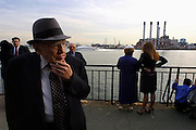 "An older Jewish man looks to the smoking remnants of lower Manhattan about ""Ground Zero"" days after the 9/11 attacks as they gather along the river in prayer."