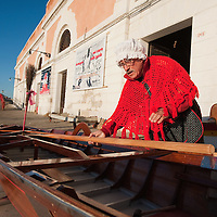 "VENICE, ITALY - JANUARY 06:  Gianni Colombo called ""timbro""  prepares his boat ahead of the 34th  Befana Regata on January 6, 2012 in Venice, Italy.  In Italian folklore, Befana is an old woman who delivers gifts to children throughout Italy on the feast of the Epiphany on January 6 in a similar way to Saint Nicholas or Santa Claus."