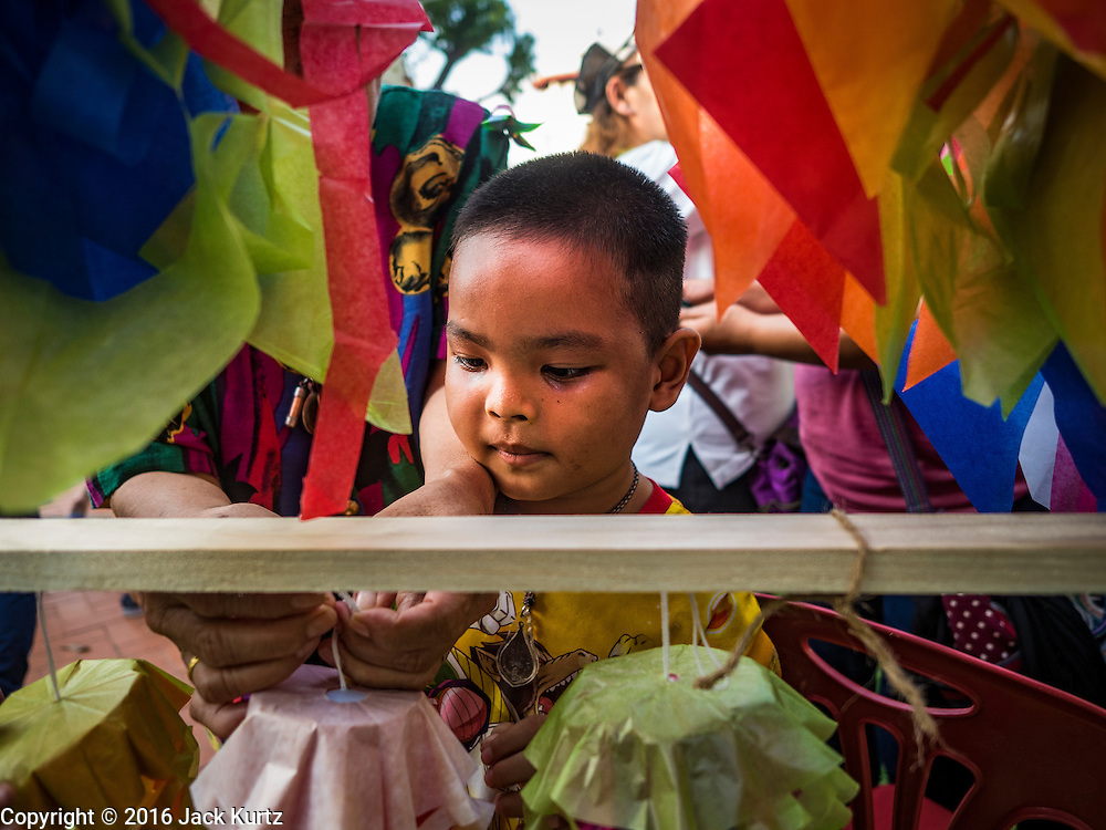 10 SEPTEMBER 2016 - BANGKOK, THAILAND: Children hang traditional Thai paper flowers in Pom Mahakan during a community party in the old fort. The flowers are hung as decorations. Forty-four families still live in the Pom Mahakan Fort community. The city of Bangkok has given them provisional permission to stay, but city officials say the permission could be rescinded and the city go ahead with the evictions. The residents of the historic fort have barricaded most of the gates into the fort and are joined every day by community activists from around Bangkok who support their efforts to stay.                PHOTO BY JACK KURTZ