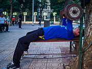 26 DECEMBER 2017 - HANOI, VIETNAM: A man lifts weights during his morning exercise session at Hoan Kiem Lake, in the Old Quarter of Hanoi. Thousands of Vietnamese people line the lake front in the early hours of the morning to perform tai chi and other low impact aerobic workouts.    PHOTO BY JACK KURTZ