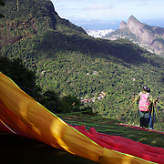 A tandem para glider prepares to take off above the hillside of Pedro Bonita high in the hills of Rio de Janeiro. Pilots of hang gliders and para gliders take tourists for tandem flights with breathtaking views of the city before landing on Sao Conrado beach. Rio de Janeiro,  Brazil. 9th September 2010. Photo Tim Clayton.