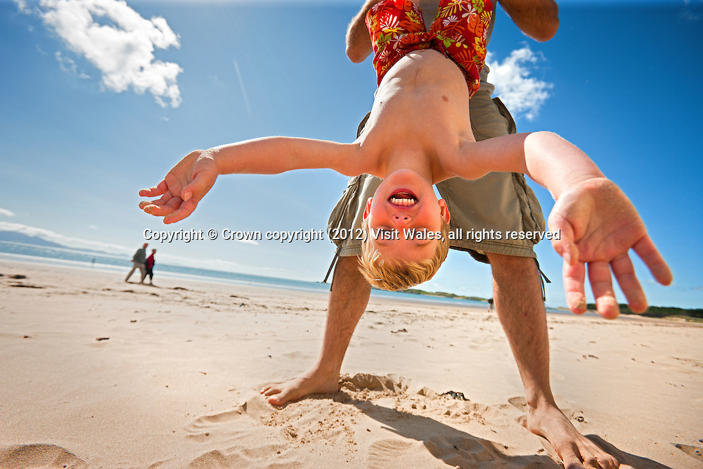 Father holding son upside down, playing on beach<br /> Newborough Beach <br /> Llanddwyn island<br /> Isle of Anglesey<br /> North<br /> Towns and Villages