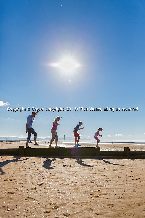 Family walking along groyne on <br /> beach<br /> Rhyl<br /> Denbighshire<br /> North<br /> People<br /> Lifestyle<br /> Towns and Villages