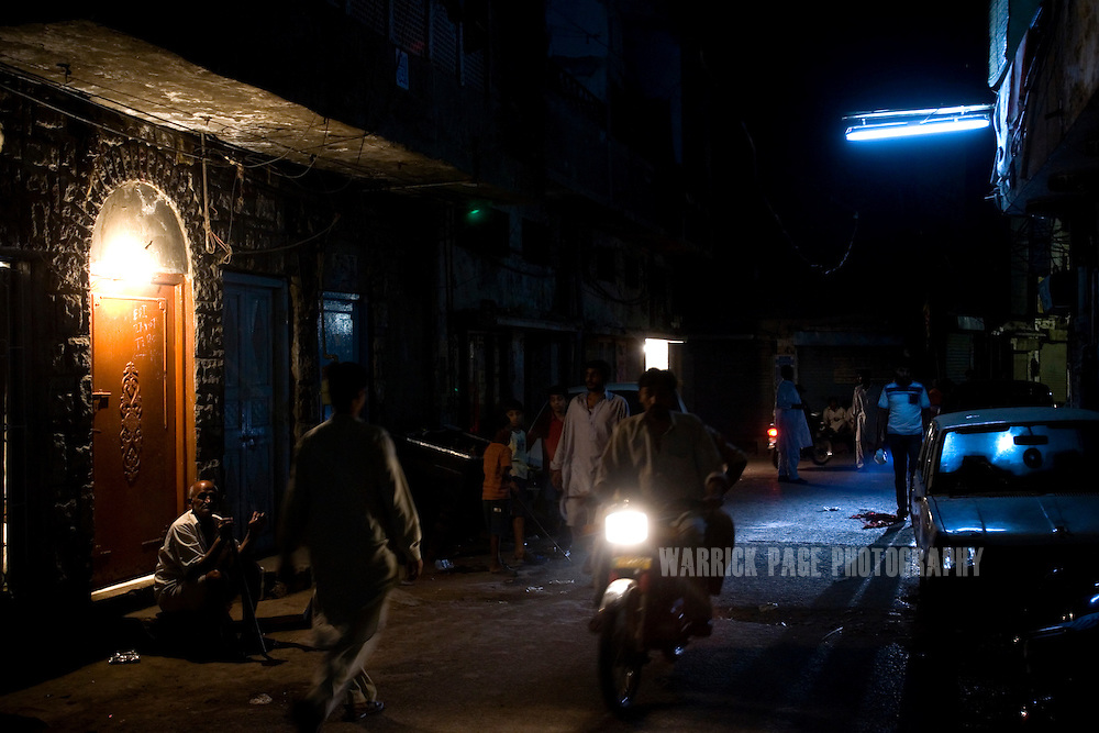 LAHORE, PAKISTAN - MAY 12: A motorcycle rides past one of the few remaining nightcliubs in Lahore's red-light district on Saturday, May 12, 2007, in Lahore, Pakistan. For nearly 60 years, Lollywood tapped the unending resource of Lahore's infamous red-light district, Heera Mandi (Urdu for Diamond Market) for their steady supply of movie heroines, today only 4 clubs remain as crime and drugs have taken over. As thawing relations between Pakistan and India lead them closer to regional stability, Pakistan's film industry takes another hit as Bollywood films dominate an already floundering institution, as the Pakistani government eases a 43-year-old ban on screening Indian films and audiences are drawn to their neighbours silver-screen theatrics. Once a thriving film industry in the chaotic and colourful city of Lahore, Pakistan's answer to Bollywood - Lollywood - is now a shadow of its former self. Two decades ago 11 studios averaged a collective 100+ films per year as cinemagoers filled more than 1000 theatres across the country. Today, only one functioning studio struggles to produce a single film for the country's 200 decaying theatres. (Photo by Warrick Page)