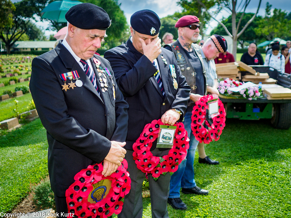 """11 NOVEMBER 2018 - KANCHANABURI, KANCHANABURI, THAILAND:  Veterans lay to wait wreaths during the Rememberance Day ceremony at the Kanchanaburi War Cemetery in Kanchanaburi, Thailand. Kanchanaburi is the location of the infamous """"Bridge On the River Kwai"""" and was known for the """"Death Railway"""" built by Japan during World War II using allied, principally British, Australian and Dutch, prisoners of war as slave labor. There are 6,982 people buried in the cemetery, including 5,000 Commonwealth soldiers and 1,800 Dutch soldiers. November 11, 2018 marked the 100th anniversary of the end of World War I, celebrated as Rememberance Day in the UK and the Commonwealth and Veterans' Day in the US.   PHOTO BY JACK KURTZ"""
