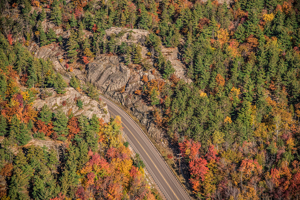 Aerial photography of  the County Road 550 rock cut in the rugged terrain north of Marquette, Michigan during fall color season.