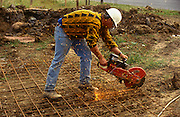 A building worker grinds steel caging on a construction project site in Milton Keynes, UK. Bending down to ground level, the workman touches his grinder to cut the steel structure into the required size and shape, destined to be covered in reinforced concrete for this generic construction project. Sparks fly up though the worker wears no protection gear against burns from the hot sparks.