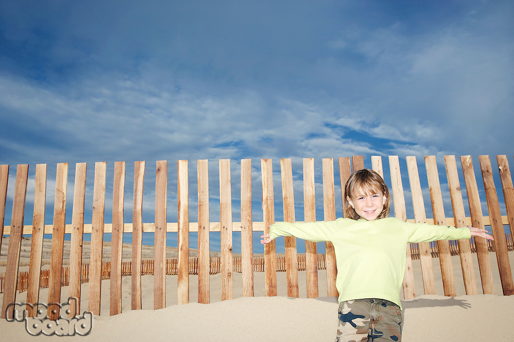 Boy (5-6) standing against wooden fence on sand dune portrait