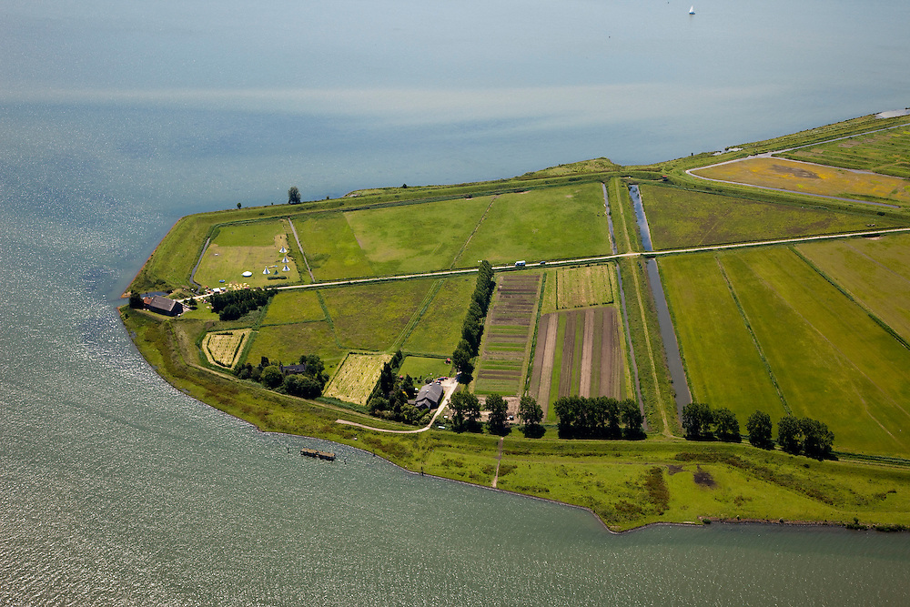 """Nederland, Zuid-Holland, Tiengemeten, 12-06-2009; Eiland in het Haringvliet, kop van het eiland in het Oosten. .Oorspronkelijk gebruikt voor de akkerbouw maar inmiddels 'teruggegeven aan de natuur', de dijken zijn deels doorgestoken, de laatste boer is in 2006 vertrokken. Huidig gebruik onder andere zorgboerderij en kan er gekampeerd worden, camping met wigwams in de voorgrond. De 'nieuwe natuur' vormt onderdeel van de Ecologische Hoofdstructuur. Oorspronkelijk was het eilandje eigendom van AMEV (Fortis Investments) - binnen de dijken, de buitendijkse slikken waren van de Vereniging Natuurmonumenten..The island Tiengemeten in the Haringvliet, originally owned - within the dikes - by AMEV (Fortis Investments), and Natuurmonumenten (Society for conservation of nature). The island was used for agriculture but has now """"been given back to nature"""", large parts have been flooded and the isle is part of the National Ecological Network. The last farmer left in 2006. Current use, among other, care farms and camping..Swart collectie, luchtfoto (25 procent toeslag); Swart Collection, aerial photo (additional fee required).foto Siebe Swart / photo Siebe Swart"""