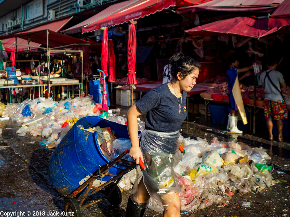 """04 DECEMBER 2018 - BANGKOK, THAILAND:  A worker hauls a barrel of trash past a pile of discarded plastic bags in Khlong Toei market. The issue of plastic waste became a public one in early June when a whale in Thai waters died after ingesting 18 pounds of plastic. In a recent report, Ocean Conservancy claimed that Thailand, China, Indonesia, the Philippines, and Vietnam were responsible for as much as 60 percent of the plastic waste in the world's oceans. Khlong Toey (also called Khlong Toei) Market is one of the largest """"wet markets"""" in Thailand. December 4 was supposed to be a plastic free day in Bangkok but many market venders continued to use plastic.     PHOTO BY JACK KURTZ"""