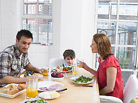Boy (5-6) eating lunch with parents at dining room table