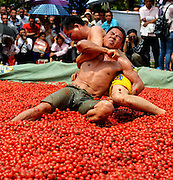 BAISE, CHINA - APRIL 14: (CHINA OUT) <br /> <br /> Two men wrestle in a cherry tomatoes pool during the Buluotuo Culture Festival on April 14, 2016 in Tianyang County, Baise City, Guangxi Zhuang Autonomous Region of China. A wrestling match was held on the surplus and cracked cherry tomatoes inside a 30-centimeter-tall pool with the diameter of 8 meters to celebrate the harvest of tomatoes during the Buluotuo Culture Festival in Tianyang. <br /> ©Exclusivepix Media
