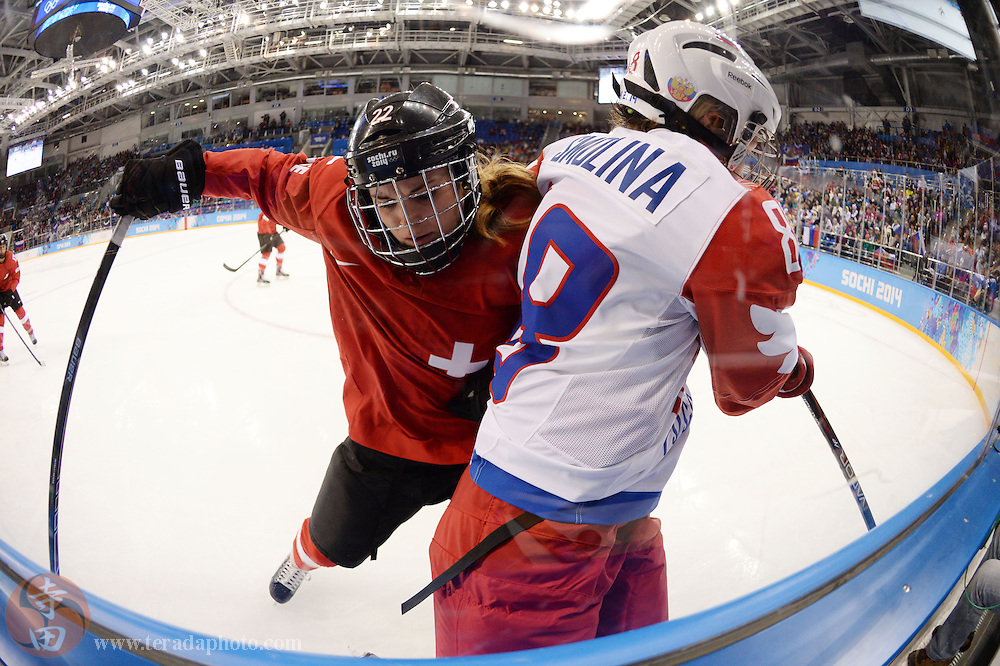 Feb 15, 2014; Sochi, RUSSIA; Switzerland defenseman Livia Altmann (22) reaches for the puck as she checks Russia forward Iya Gavrilova (8) in a women's quarterfinals ice hockey game during the Sochi 2014 Olympic Winter Games at Shayba Arena.
