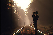 Sri Lanka..The railway tracks that run south past the City of Galle. .Father and son on the tracks in the early morning. The railway system in the country was built during the British Colonial period..Copyright: Dominic Sansoni