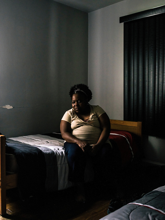 Patricia Lowe, mother of Edward, sits on his bed in his room. Edward is incarcerated in Detroit.
