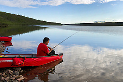 Tristen Jade Lockhart, 14, fishes  as the Dene First Nation youth paddle down the Thelon river In the middle of the largest and most remote game sanctuary in North America, in the Northwest Territories, just south of the Arctic Circle. Its fate now hangs in the balance, protected on paper, but with little management, no money, and no voice for the Dene, its most ardent advocate for protection, while mining (for diamonds, gold, and uranium) threats, buoyed by recent prices, loom.  Dene youth have rarely been deep into the Thelon, yet the caribou is still their life blood, reverentially important.  These Dene are amongst the last hunter/gatherers in the Northern Hemisphere.   (Photo by Ami vitale)