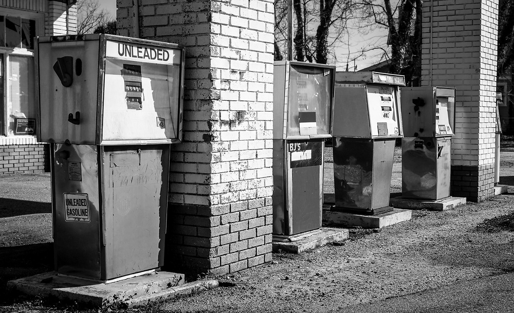A line of old gas pumps stand as monuments at this abandoned old gas station. A slightly wide angle lens and low shooting height create a nice perspective.