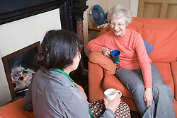 IndependentAge volunteer and older woman enjoying a cup of tea together,