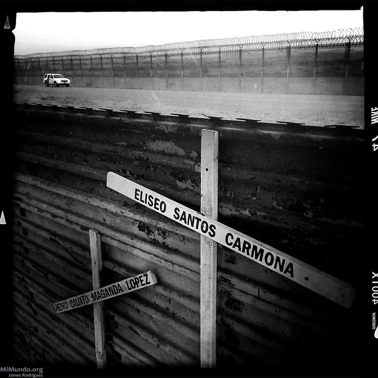 Two crosses with the names of missing migrants hang on the Mexican side of the Mexico-US border wall while a US border patrol awaits  in a buffer zone between the two walls. Tijuana, Baja California, Mexico. May 30, 2015.