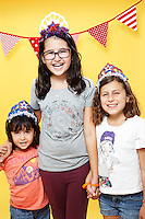 3 girls wearing red white and blue tiara's atnding against yellow seamless.<br /> Photographed at the Photoville Photo Booth September 20, 2015