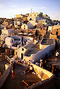 Greece, Cyclades, Santorini, sunset watchers in town of Oia.