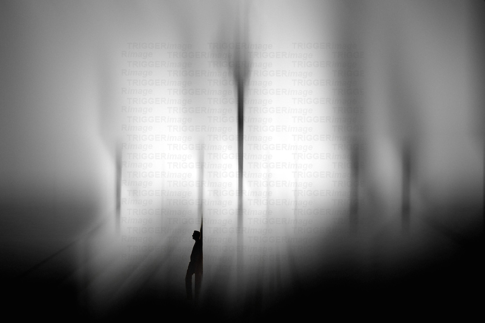 Silhouetted male figure alone in backlit scene
