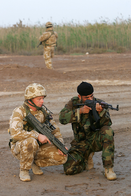 30th April 2006..Basra, Iraq..Iraq/Iran Border Enforcement..British soldiers from the 9/12 Lancers work alongside Iraqi Security Forces along the Iraq/Iran border. The task is to combat smuggling of people, weapons and fuel across the river...An Iraqi commando based at a riverside border fort on the Shat al-Arab waterway between Iraq and Iran undergoes some instruction whilst on a joint patrol with British troops.....