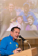 Boston Marathon race director Dave McGillivray speaks at a special meeting of the  Orange Runners Club at Kuhl's Highland House in Middletown, New York. A photograph of McGillivray and his family near the finish line of the 2013 Boston Marathon is on the screen in the background.