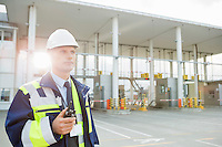 Middle-aged male worker holding walkie-talkie while looking away in shipping yard