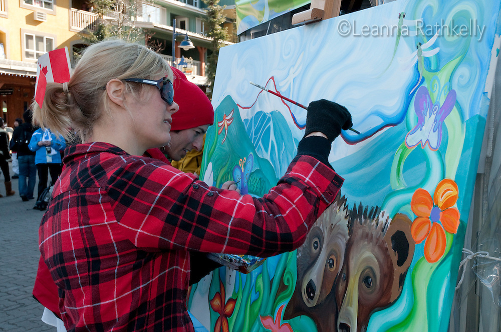 Artists Vanessa Stark and Oliver Roy paint in the Town Plaza as part of Whistler Live during the 2010 Olympic Winter Games in Whistler, BC Canada.